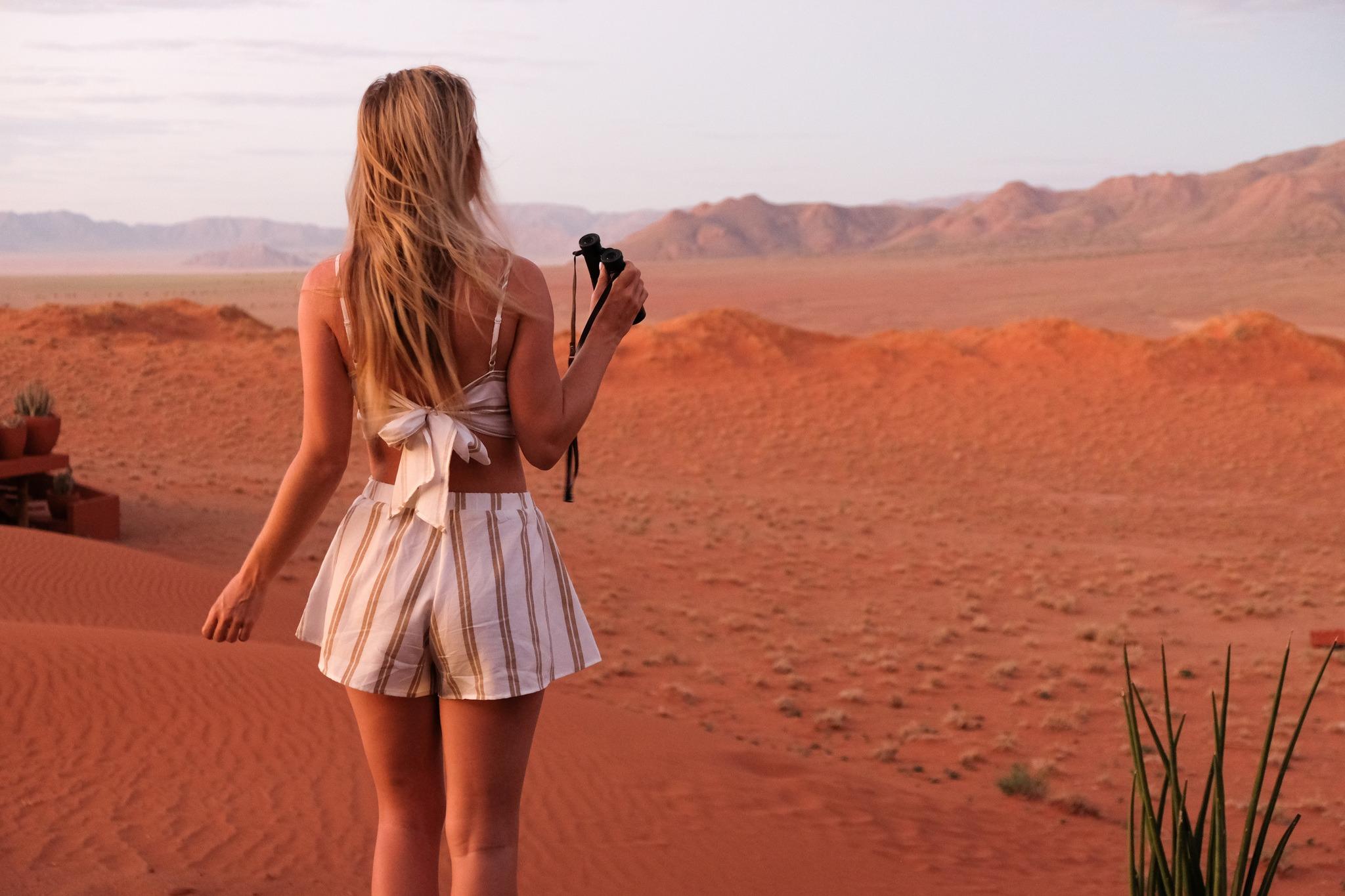 blonde with binoculars in namib desert