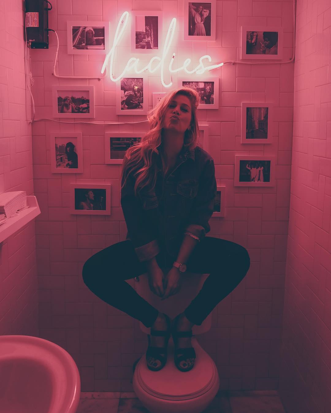 ladies neon pink sign in bathroom